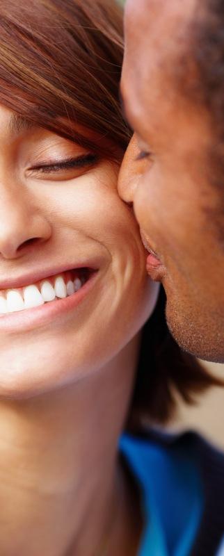 Smiling man kissing his happy girlfriend